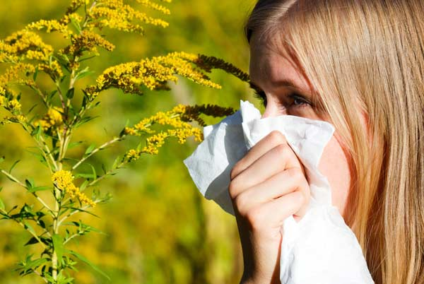 Woman with allergy in field